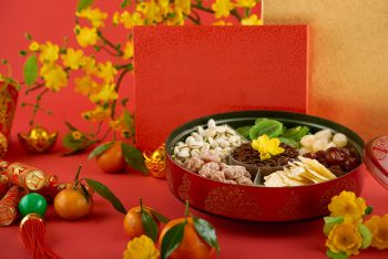 Round tin box with dried fruits, nuts, roasted melon seeds, crackers with best wishes inscription and tangerines for Lunar New Year celebration
