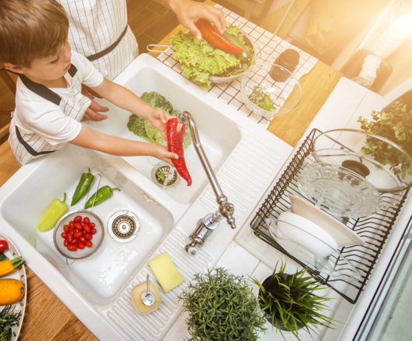 Young child washing veggies in the sink