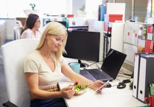 woman eating lunch alone at desk
